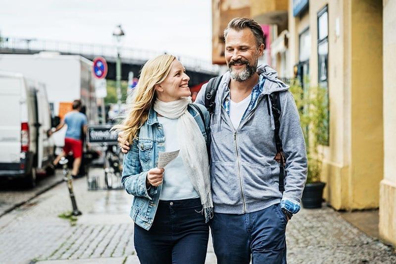 Couple Walking Alone On A Sidewalk