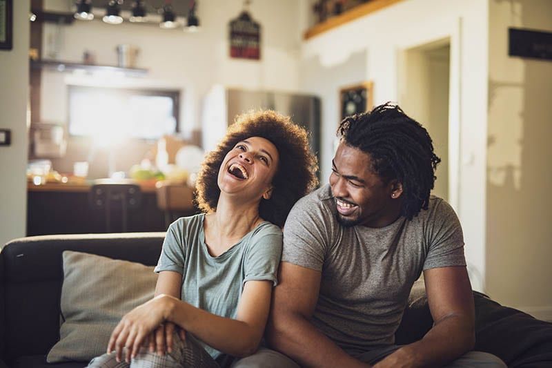 Cheerful black couple having fun while relaxing on sofa at home.