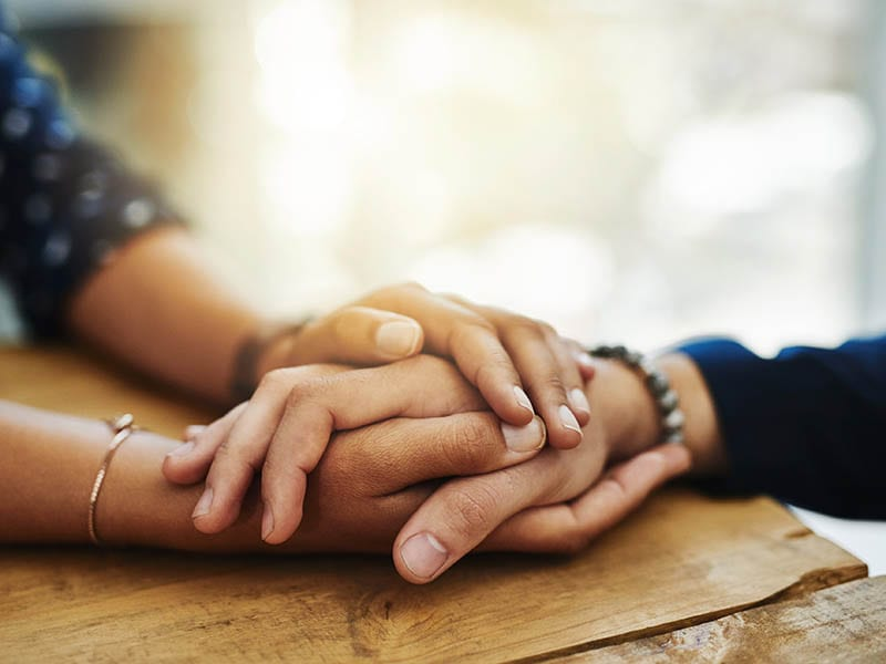 Closeup shot of two unrecognizable people holding hands in comfort