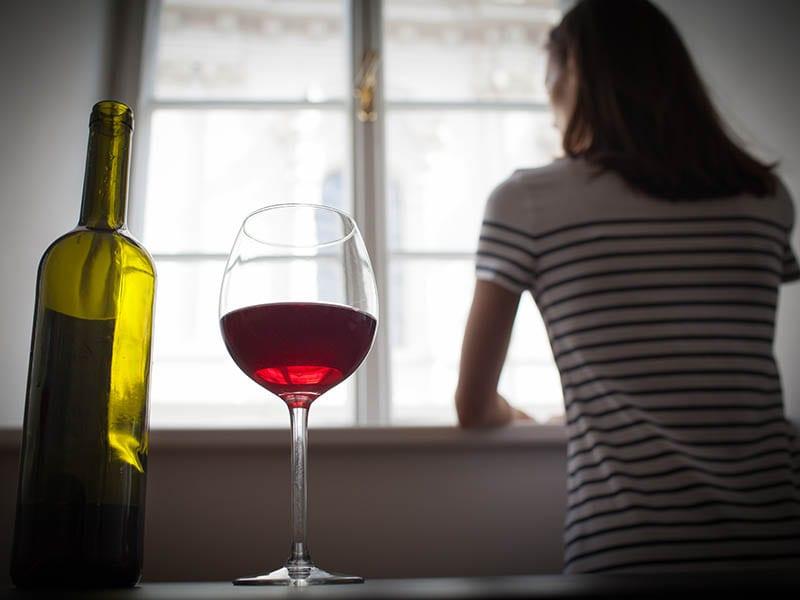 Woman drinking wine alone in the dark room