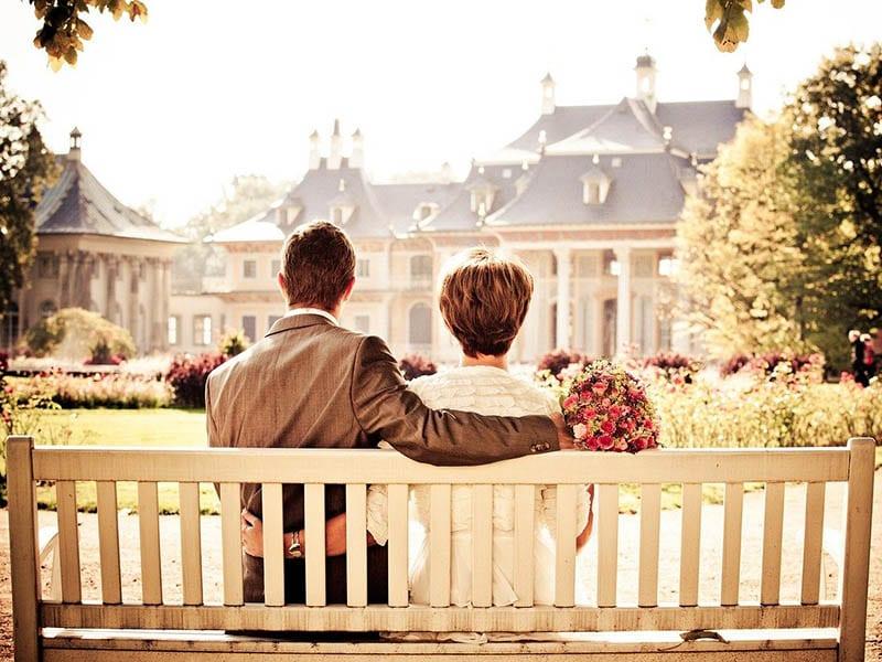 Older lovers embrace on park bench