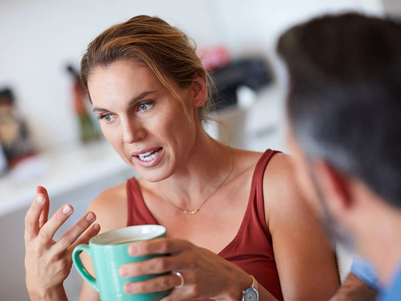 Cropped shot of an attractive young woman having a serious conversation with her husband while holding a cup of coffee